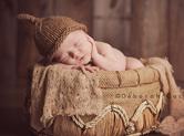 Photo nouveau-ne Photo teintes marron de bébé dans une corbeille